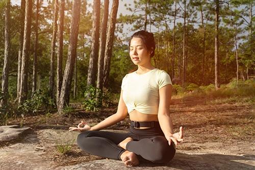 femme en méditation dans la forêt